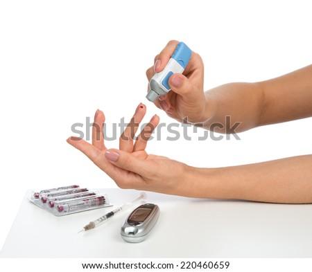 Diabetes diabetic concept finger prick for glucose sugar measuring level blood test on white background - stock photo