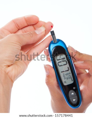 Diabetes patient measuring glucose level blood test using ultra mini glucometer and small drop of blood from finger and test strips isolated on a white background
