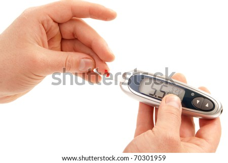 Diabetic patient measuring glucose level blood test using ultra mini glucometer and small drop of blood from finger and test strips isolated on a white background. Device shows normal blood-level - stock photo