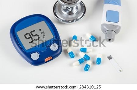 Diabetic test kit and stethoscope on white background - stock photo