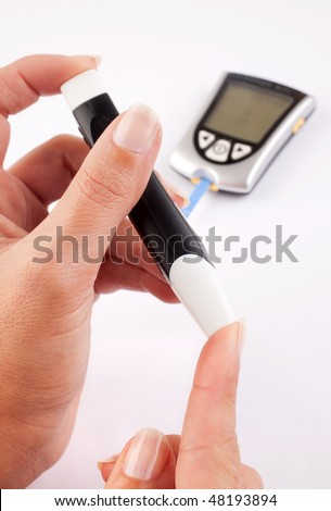 Diabetic woman pricking her finger for a blood test with a glucometer in the background - stock photo