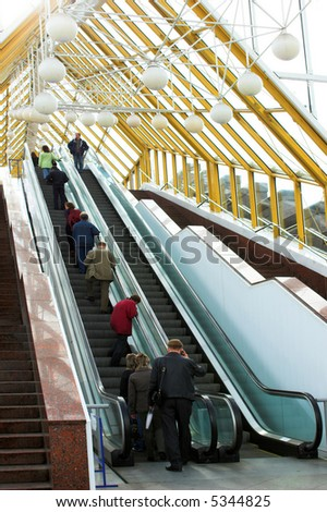 diagonal escalators stairway in center, moving people and spheres on roof - stock photo