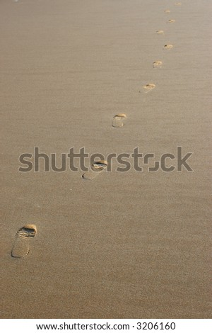 Diagonal line footsteps on the sand - stock photo