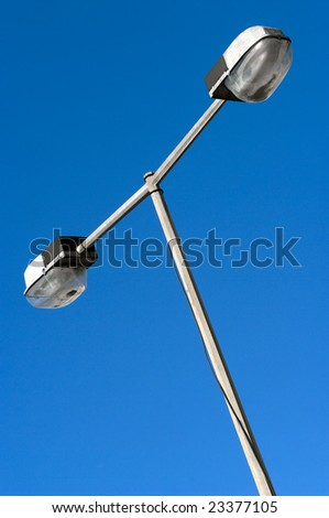 Diagonal perspective of a streetlamp against a deep blue sky. - stock photo
