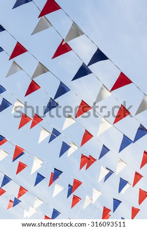 Diagonal red white and blue triangular bunting against a blue sky on a sunny day - stock photo