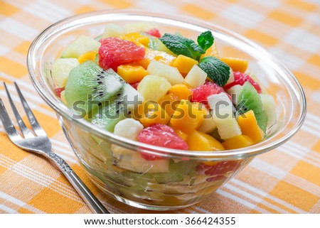 Diagonally in the center glass bowl with fruit salad of mango, pineapple, grapefruit, banana and kiwi on yellow checkered tablecloth. Fruit exotic salad with fork. Daylight. Horizontal.