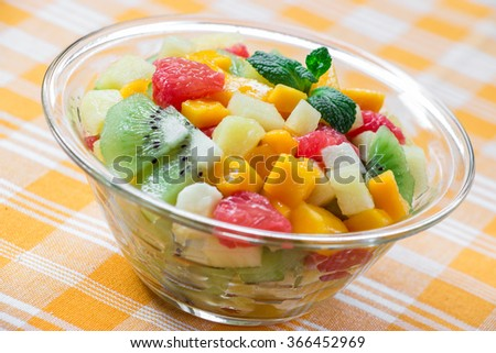 Diagonally in the center glass bowl with fruit salad of mango, pineapple, grapefruit, banana and kiwi on yellow checkered tablecloth. Fruit exotic salad with spoon. Daylight. Horizontal. Close.