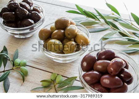 Diagonally of horizontal frame 3 glass bowls with different kinds of olives framed by branches of the olive tree on wooden white background. 3 kinds of olives. Daylight. Horizontal shot. - stock photo