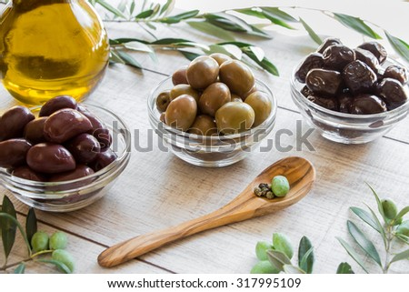 Diagonally of horizontal frame 3 glass bowls with different olives, bottle of olive oil, spoon with olive, framed by branches of the olive tree on wooden white. 3 kinds of olives and olive oil. - stock photo