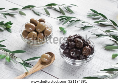 Diagonally of horizontal frame in row 2 glass bowls with different kinds of olives framed by branches of the olive tree on wooden white background. 2 different kinds of olives and spoon. Daylight. - stock photo