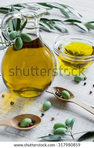 Diagonally of vertical frame bottle of olive oil, bowl with the olive oil and olives on white background of olive branch, in the frame 2 wooden spoons with olives. Olive oil vertical frame.    - stock photo