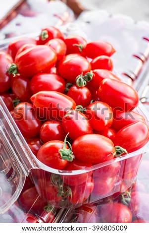 Diagonally opened plastic container of selective cherry tomatoes ready for sale in vegetable shop. Packed cherry tomatoes. Vertical. Daylight. Close.