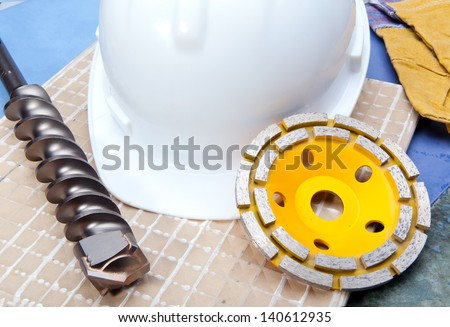 Diamond discs for cutting of tile and a helmet on a tile  - stock photo