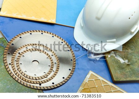 Diamond discs for cutting of tile, goggles and a helmet on a tile - stock photo