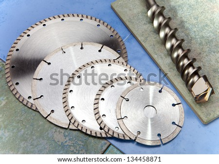 Diamond disk, drill and a helmet on a tile - stock photo
