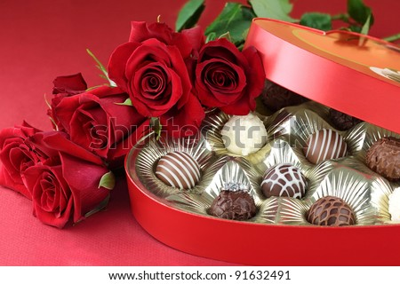 Diamond engagement inside of a heart shaped box of chocolate truffles with red roses. Selective focus on diamond ring with soft blurred background. - stock photo
