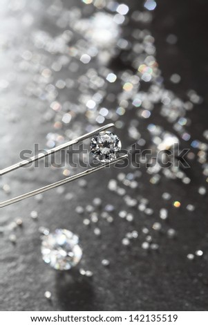 diamond held by tweezers close up. more diamonds out of focus in background.  - stock photo