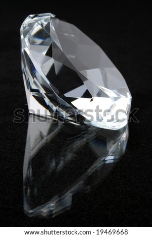 Diamond on black reflective surface - stock photo
