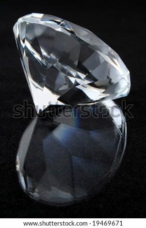 Diamond on black reflective surface - stock photo
