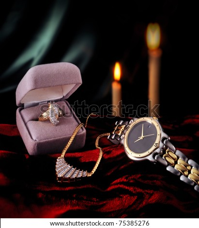 Diamond ring, gold watch, and necklace on green and red with candle