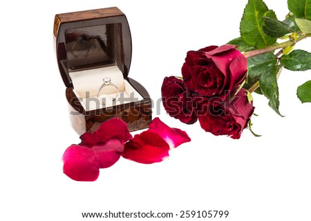 Diamond ring in box with red rose on white background