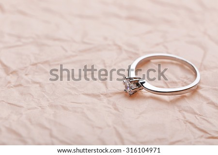 Diamond ring on a pink paper background