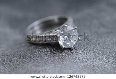 diamond ring on elegant gray leather background - stock photo