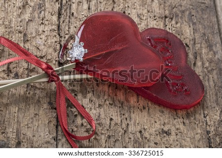diamond ring with heart shaped candies on wood - stock photo