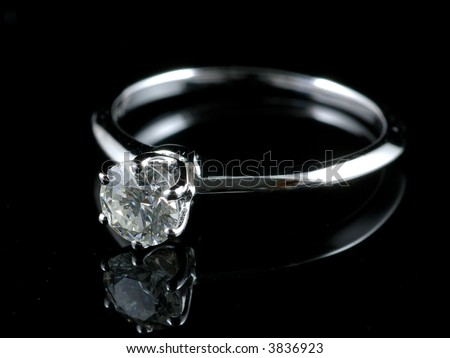 Diamond ring with reflection in isolated black background - stock photo