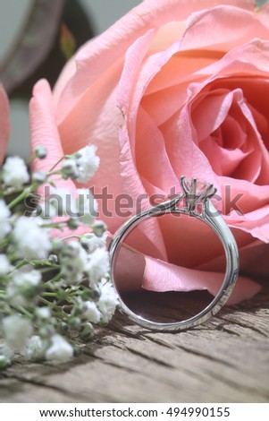 Diamond ring with roses on wooden surface