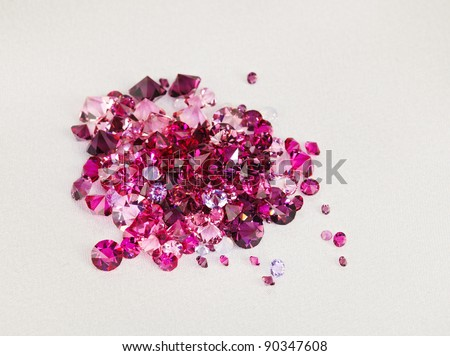 Diamond (ruby) stones heap over cream silk cloth background - stock photo