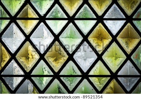 diamond shaped pattern of a stained glass window - stock photo