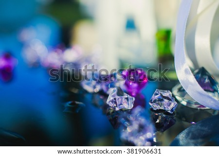 Diamond (small purple jewel) stones heap over mirror glass table, crystal stones, shiny gold and silver jewelery on a table