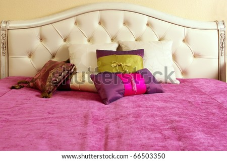 diamond upholstery buttons bed head pink blanket colorful pillows - stock photo