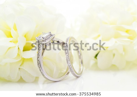 Diamond white gold ring. White Flower background