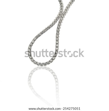 Diamonds necklace close up on white background with reflection - stock photo