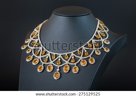 diamonds with yellow sapphire necklace on the black background - stock photo