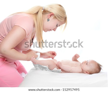 Diaper changing - hygiene concept. Young mother solving an smelly diaper accident.  - stock photo