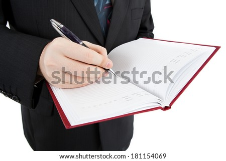diary and human hand holding a pen close-up isolated