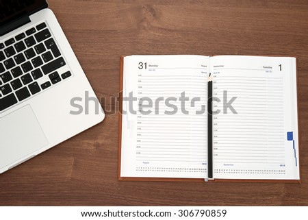Diary and laptop on wooden table, top view - stock photo