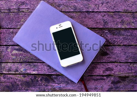 diary and mobile phone  on the old desk - stock photo