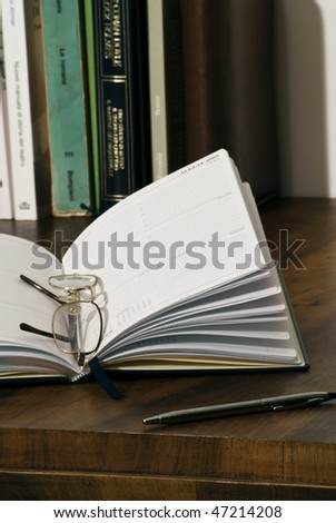 Diary, books, silver pen and glasses