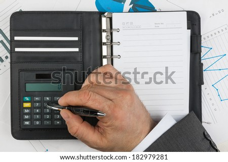 Diary, calculator,hand and pen  on a background of diagrams and graphs