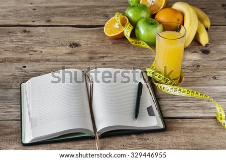 diary for records with fruit and a glass of fresh juice on a wooden table. Top view. The concept of a healthy lifestyle and diet recipe - stock photo