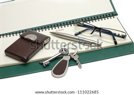 Diary, glasses and keys on a white background - stock photo