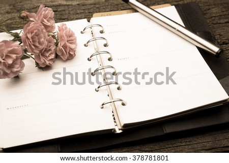 Diary note with rose on old wood  in vintage style (Organizer ,agenda, book, diary) - stock photo