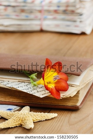 Diary, old letters and red freesia flower on wooden table. Romantic vintage setting. Copy space