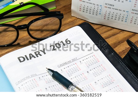 Diary planner book 2016 in black leather case open calendar page with glasses and pen on the wooden table - stock photo