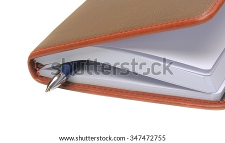 Diary with a pen between pages, shallow DOF - stock photo