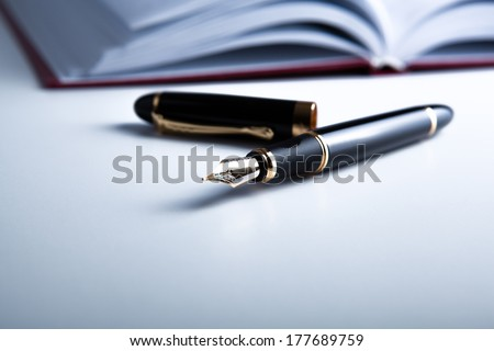 diary with fountain pen on white close-up - stock photo